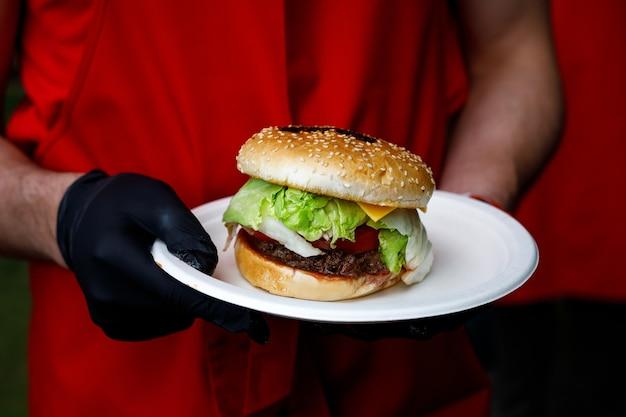 L'uomo tiene in mano un gustoso hamburger pronto in guanti neri.