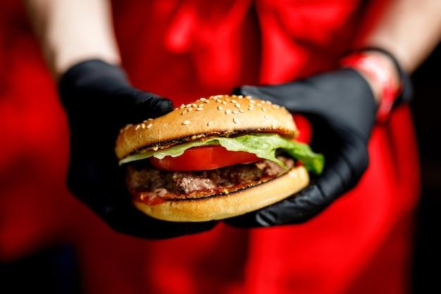 L'uomo tiene pronto gustoso hamburger nelle mani in guanti neri.