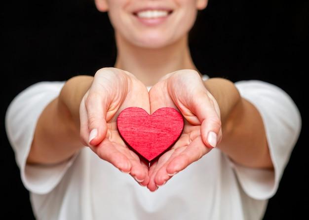 L'uomo tiene il cuore rosso nelle sue mani sullo sfondo di vestiti leggeri