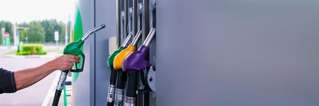 L'uomo tiene in mano una pistola per il rifornimento di carburante per le auto. stazione di servizio con il primo piano del carburante diesel e benzina.