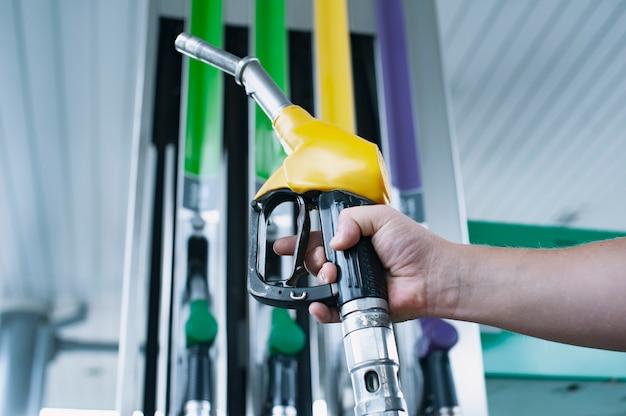 L'uomo tiene in mano una pistola per il rifornimento di carburante per le auto