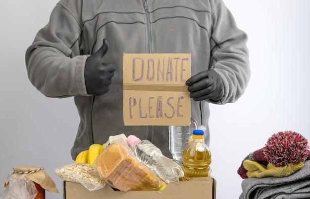 L'uomo tiene un foglio di carta con una scritta per favore e raccoglie cibo, frutta e cose in una scatola di cartone per aiutare i bisognosi e i poveri, il concetto di aiuto e volontariato