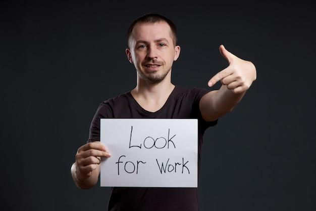 L'uomo tiene un cartello con le parole in cerca di lavoro, disoccupazione e crisi