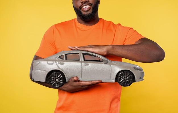 L'uomo tiene una piccola automobile. concetto di acquistare una nuova automobile