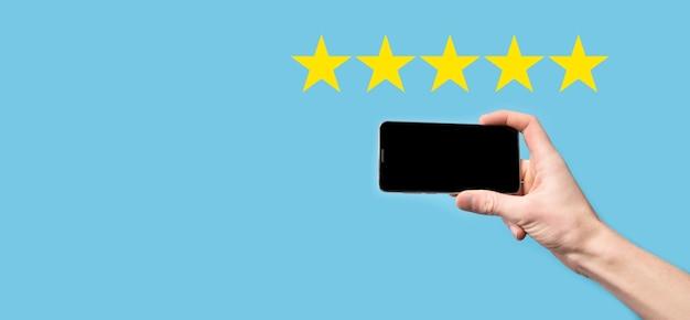 L'uomo tiene lo smart phone nelle mani e dà una valutazione positiva, icona simbolo a cinque stelle per aumentare la valutazione del concetto di azienda su sfondo blu. esperienza di servizio clienti e sondaggio sulla soddisfazione aziendale.