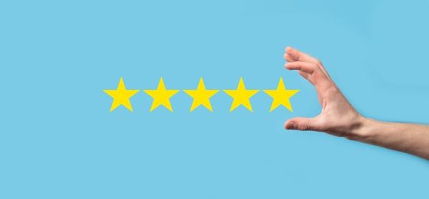 L'uomo tiene in mano lo smartphone e dà una valutazione positiva, icona simbolo a cinque stelle per aumentare la valutazione del concetto di azienda su sfondo blu. esperienza del servizio clienti e sondaggio sulla soddisfazione aziendale.