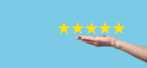 L'uomo tiene lo smart phone in mano e dà una valutazione positiva, icona simbolo a cinque stelle per aumentare la valutazione del concetto di azienda sulla superficie blu