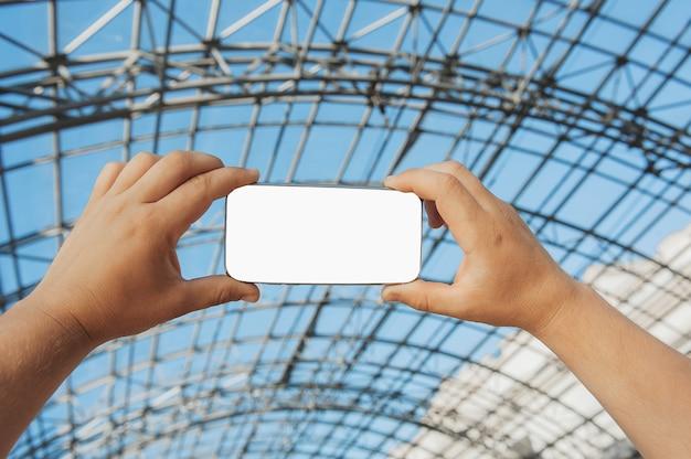 Un uomo tiene in mano uno smartphone sullo sfondo di una struttura in ferro.