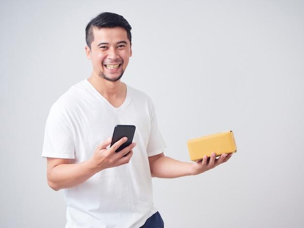 L'uomo tiene smartphone e cassetta dei pacchi
