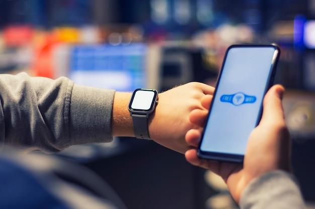 L'uomo tiene uno smartphone con un'icona wi-fi del primo piano e un orologio intelligente sulla sua mano.