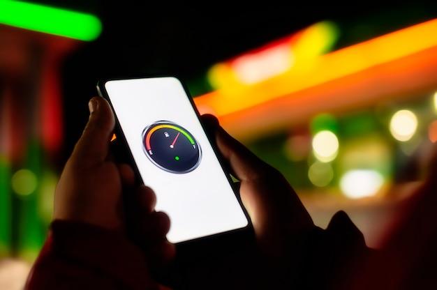 L'uomo tiene uno smartphone con un misuratore di carburante digitale sullo schermo sullo sfondo di un distributore di benzina notturno per un'auto.