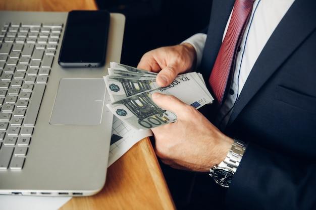 Un uomo tiene una pila di contanti e la conta in primo piano. vista laterale