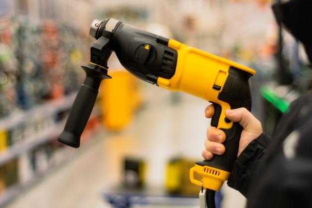 L'uomo tiene un trapano giallo nelle sue mani per i lavori di riparazione sullo sfondo delle vetrine in un negozio di ferramenta.