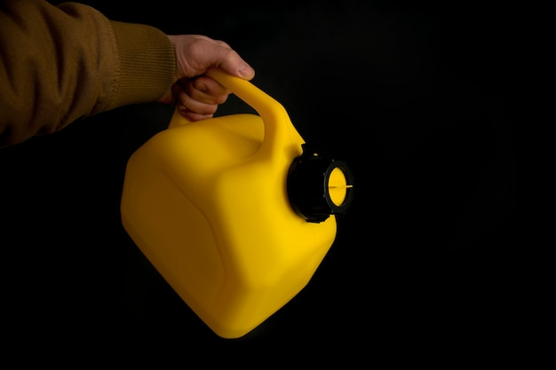 L'uomo tiene in mano una tanica di plastica gialla per carburante per auto su uno sfondo nero. mockup di un contenitore per liquidi e combustibili pericolosi.