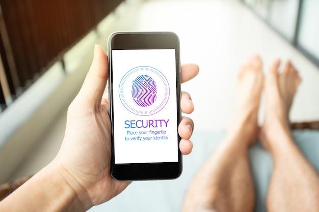 Uomo in vacanza che utilizza lo smartphone per firmare una password tramite fingertip. concetto di sicurezza mobile.