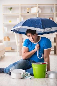 Uomo a casa che si occupa della perdita di inondazione vicina