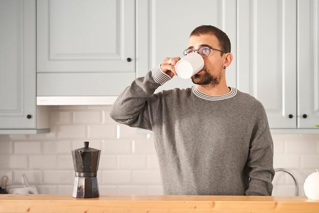 Uomo a casa che mangia caffè
