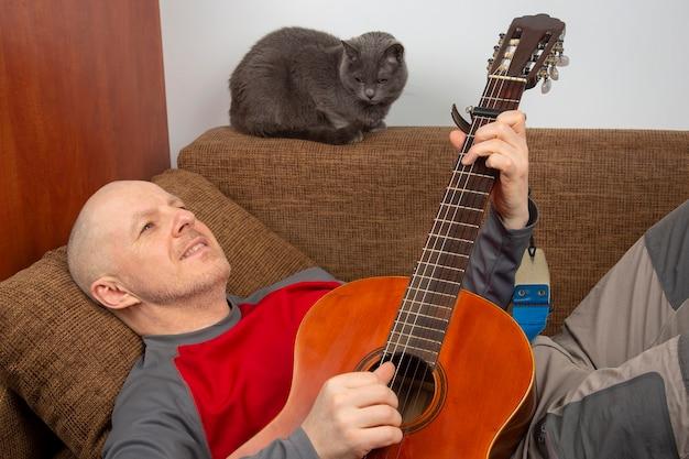 Un uomo a casa suona una chitarra classica accanto a un gatto grigio