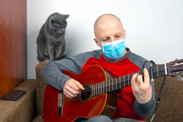Un uomo in casa in quarantena a causa di un'epidemia di coronavirus suona una chitarra classica accanto a un gatto grigio