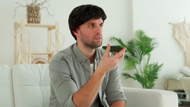 Uomo a casa seduto sul divano che invia un messaggio vocale al telefono.