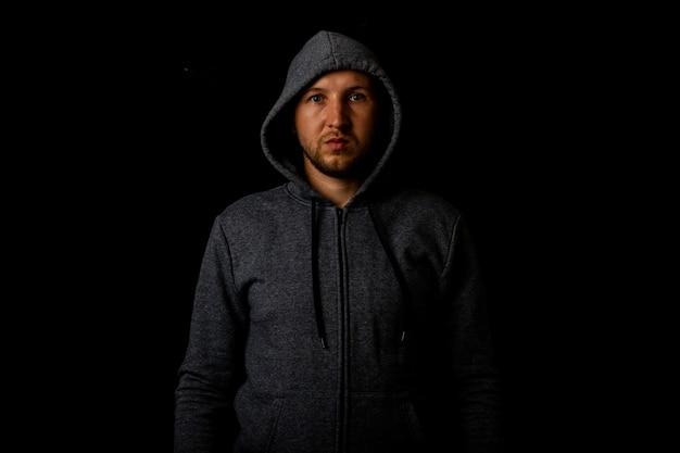 Uomo in un cappuccio e una felpa con cappuccio su uno sfondo scuro.