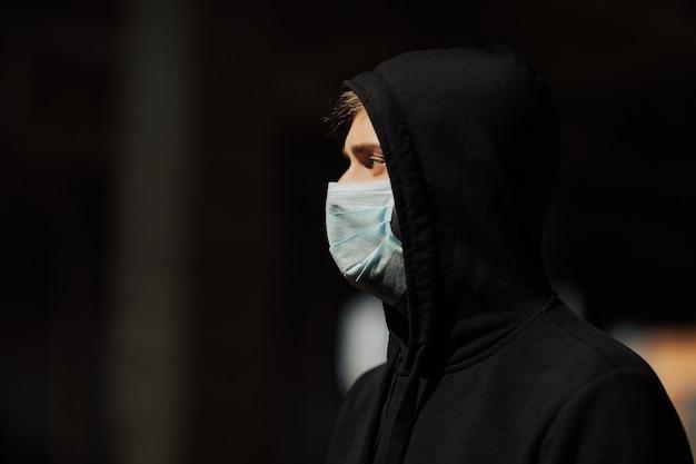 Uomo in cappuccio con maschera per proteggerlo dal coronavirus.