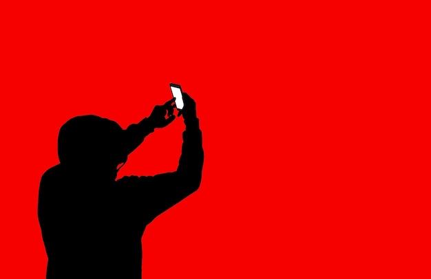 Uomo in felpa con cappuccio con un telefono isolato su sfondo rosso. dipendente da internet e dai social network. il tipo sta hackerando dati personali.