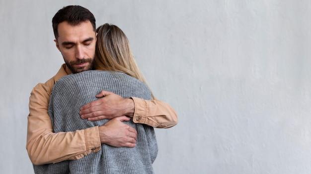 Uomo che abbraccia la donna della sabbia in una sessione di terapia di gruppo con lo spazio della copia