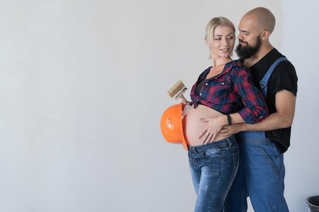 Un uomo abbraccia la moglie incinta. uniforme da lavoro e casco di sicurezza arancione. la famiglia felice fa lavori di ristrutturazione. copia spazio.