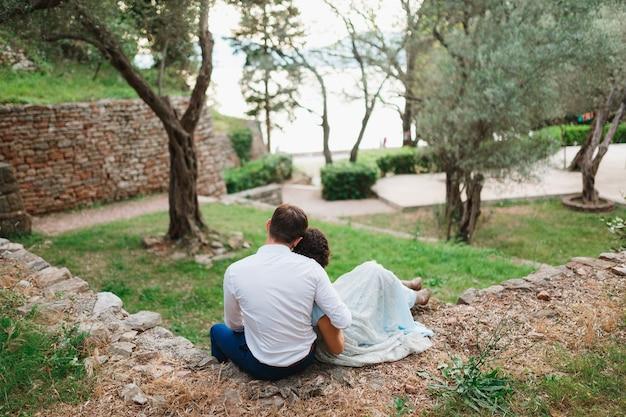 L'uomo abbraccia la donna per le spalle mentre è seduto su una recinzione di pietra tra alberi verdi in un uliveto