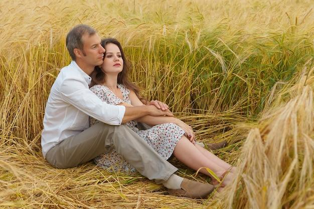L'uomo abbraccia la donna su un campo di grano, coppia d'amore, appuntamento romantico, famiglia felice