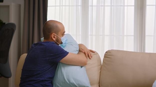 Uomo infetto da covid-19 che indossa una maschera e abbraccia un cuscino durante il blocco.