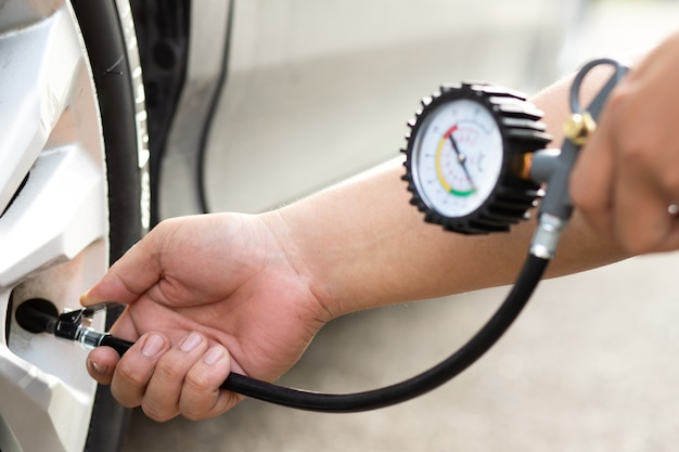 L'uomo gonfia il pneumatico e controlla la pressione dell'aria con il manometro