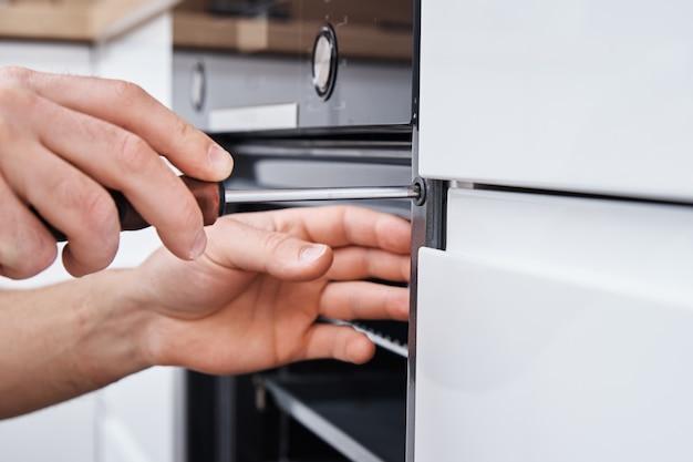 Uomo che installa il forno elettrico in cucina