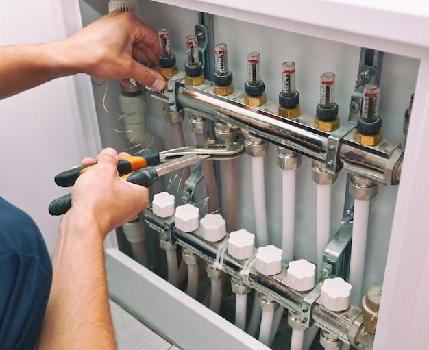 Uomo che installa il sistema di riscaldamento in casa