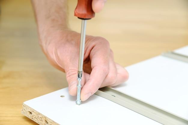 Uomo che installa i bulloni del connettore del giunto nella scheda del mobile