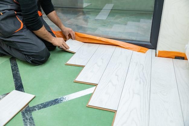 Uomo che installa un nuovo pavimento in legno laminato