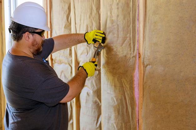 Uomo che installa uno strato di isolamento termico sotto il muro utilizzando lana minerale con fibra di vetro soft focus freddo