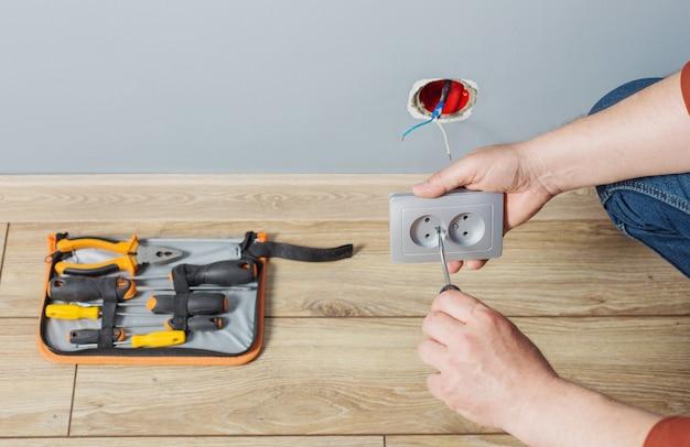 L'uomo installa una presa elettrica sul muro grigio