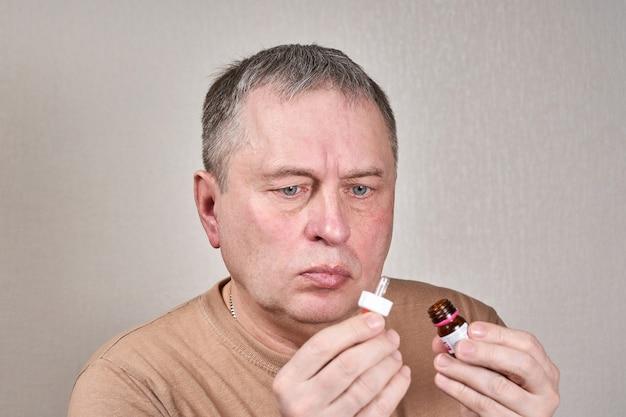 Un uomo si instilla la medicina nell'orecchio con una piccola pipetta da una bottiglia di farmacia