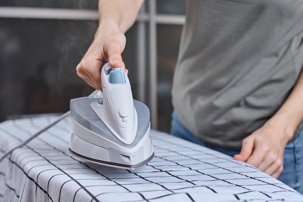 Uomo a stirare i vestiti sull'asse da stiro con ferro moderno