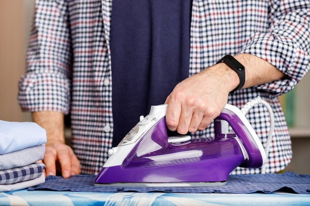 Un uomo stira una camicia su un asse da stiro con un ferro da stiro. faccende domestiche quotidiane.