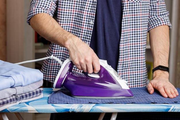 Un uomo stira una camicia su un asse da stiro con un ferro da stiro