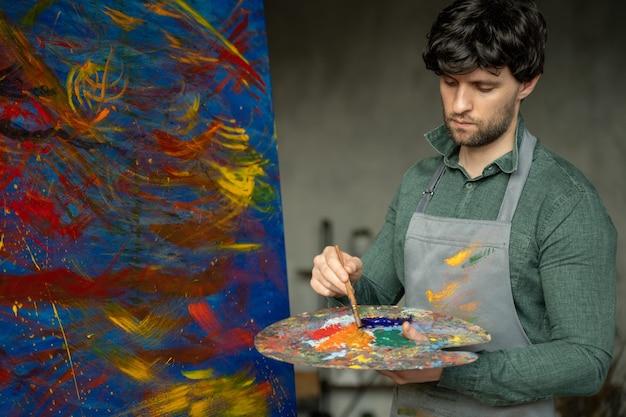 L'uomo è un artista che tiene in mano un pennello e disegna un'immagine astratta