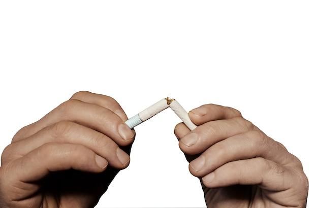 L'uomo sta rompendo la sigaretta isolata su fondo bianco. smettere di fumare. rifiuta per cattiva abitudine. pericoloso. problemi sociali e sanitari.