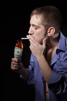 L'uomo sta bruciando una sigaretta la banconota da un dollaro.