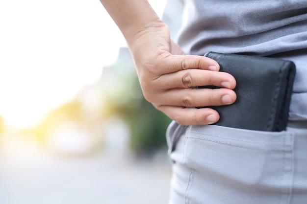 Un uomo sta portando una borsa nera piena di soldi fuori dalla tasca posteriore dei suoi pantaloni.