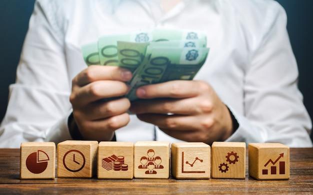 Un uomo conta soldi e blocchi con attributi aziendali. buon modello di business. redditività