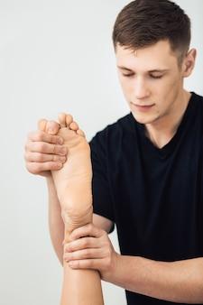 L'uomo sta facendo massaggio ai piedi alla bella giovane donna alla spa. concetto di stile di vita sano.