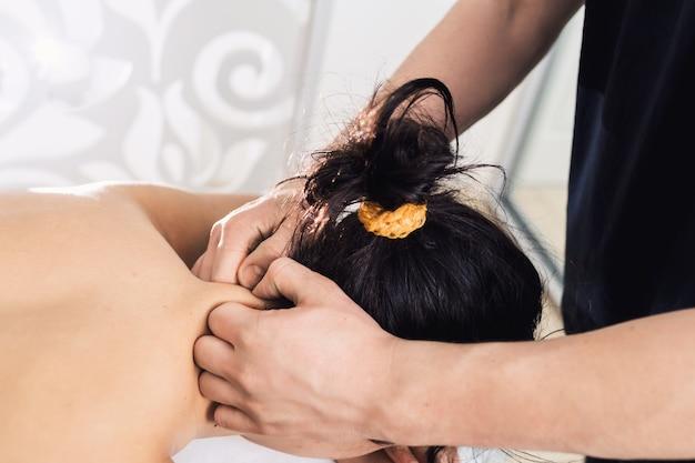 L'uomo sta facendo il massaggio al collo alla bella giovane donna alla spa. concetto di stile di vita sano.